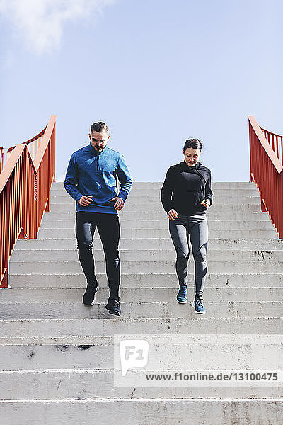 Low angle view of couple exercising on steps against sky