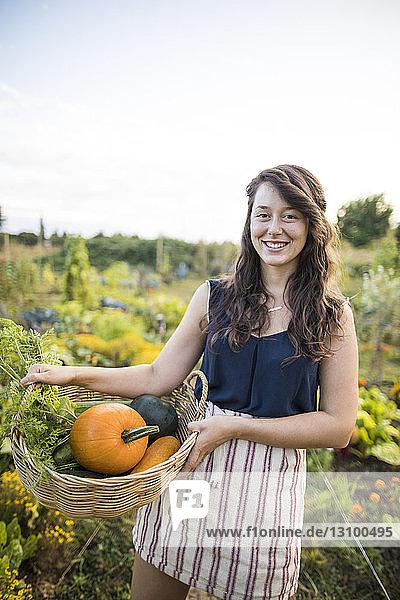 Porträt einer glücklichen Frau  die Gemüse in einem Korb gegen den klaren Himmel im Gemeinschaftsgarten trägt Porträt einer glücklichen Frau, die Gemüse in einem Korb gegen den klaren Himmel im Gemeinschaftsgarten trägt