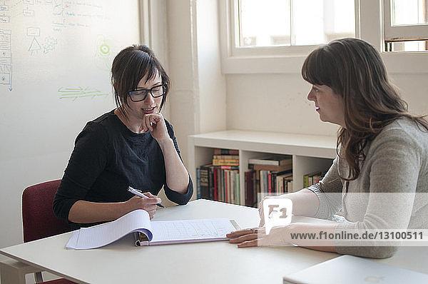 Geschäftsfrauen diskutieren während einer Sitzung am Schreibtisch im neuen Büro