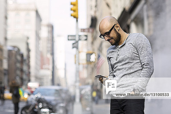 Happy man using smart phone while standing on street