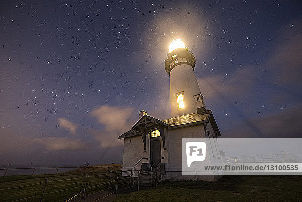 Low angle majestic view of illuminated lighthouse against star field at Cape Blanco State Park