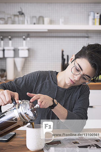 Woman pouring coffee in cup at table