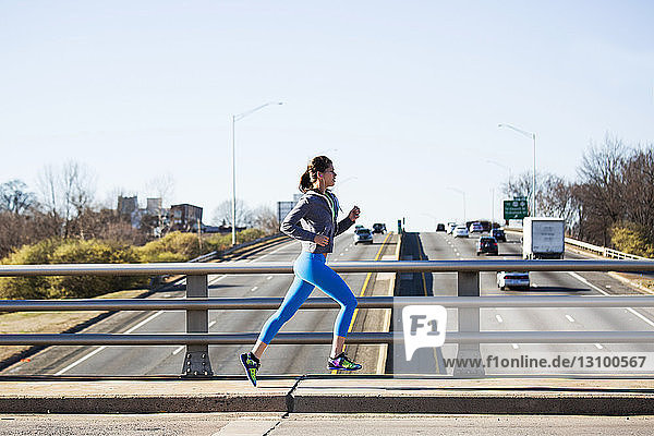 Side view of woman running on footpath against clear sky in city