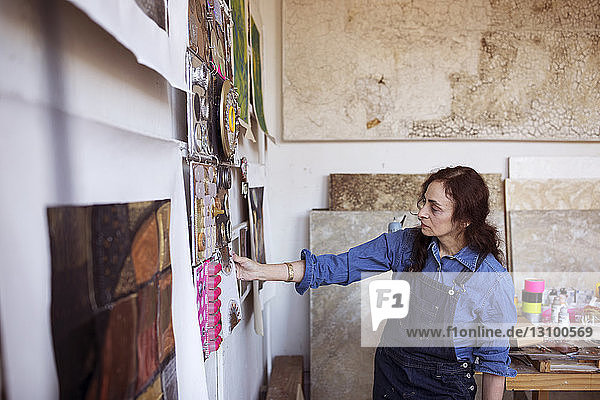 Artist looking paintings on wall in workshop