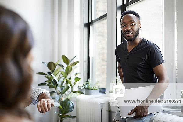 Geschäftsmann mit Laptop-Computer im Gespräch mit Kollegen im Büro