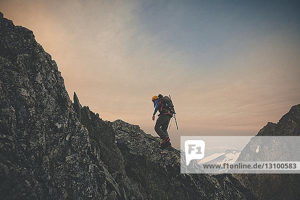 Wanderer klettert bei Sonnenuntergang in voller Länge gegen den Himmel