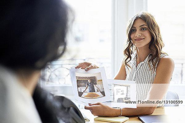 Zuversichtliche Geschäftsfrau zeigt einer Amtskollegin Fotoausdrucke