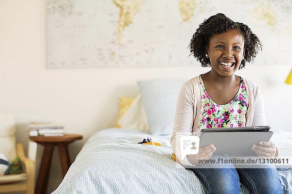 Glückliches Mädchen mit Tablet-Computer  das auf dem Bett sitzend wegschaut