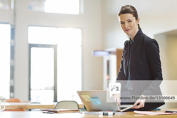 Porträt einer selbstbewussten Geschäftsfrau mit Laptop-Computer  die im Büro auf dem Tisch sitzt