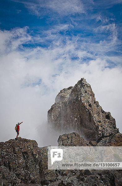 Hochwinkelansicht eines Wanderers  der auf den Berg zeigt  während er auf einem Felsen inmitten von Wolken steht