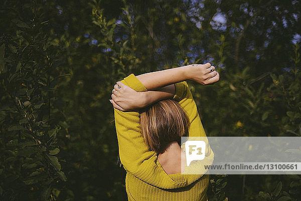 Rückansicht einer Frau mit erhobenen Armen  die bei Pflanzen im Wald steht