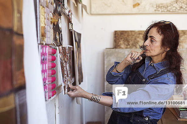 Female artist looking paintings on wall in workshop
