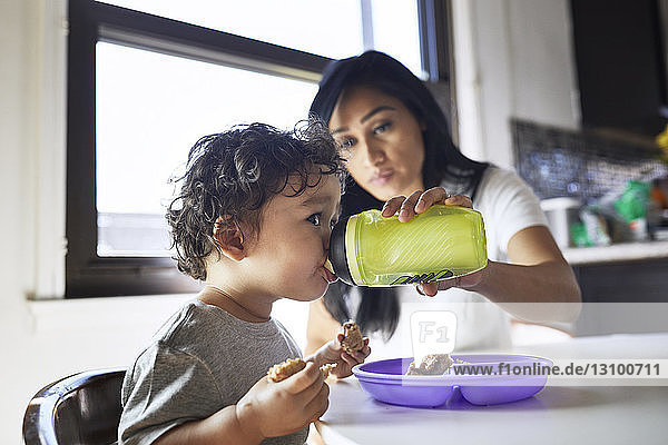 Mother feeding water to son from bottle at home