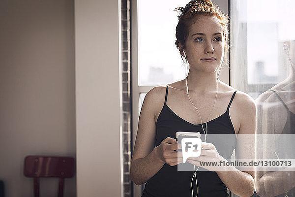 Nachdenkliche Frau schaut weg  während sie zu Hause am Fenster Musik hört
