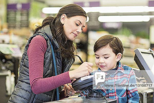 Mutter mit Sohn an der Kasse im Supermarkt