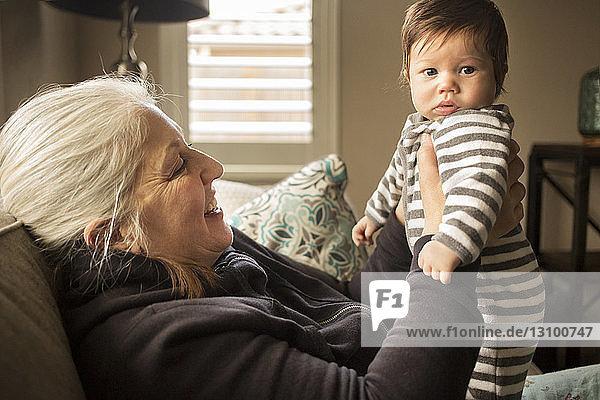 Großmutter hält Baby-Enkel zu Hause auf dem Sofa