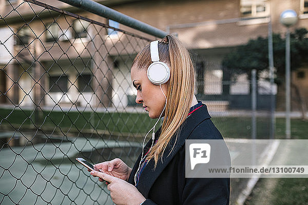Side view of woman using mobile phone while standing by fence