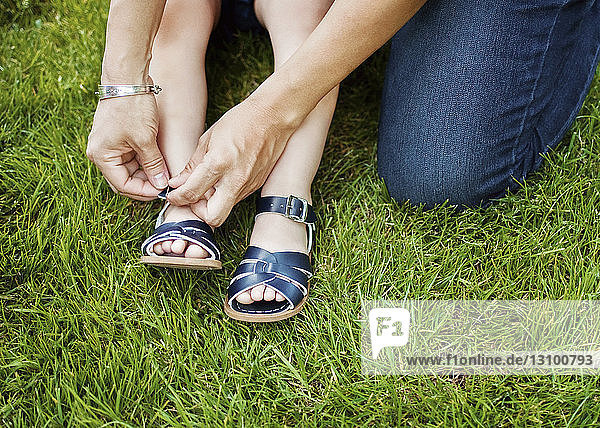 Cropped image of mother putting sandal on girl's leg on field
