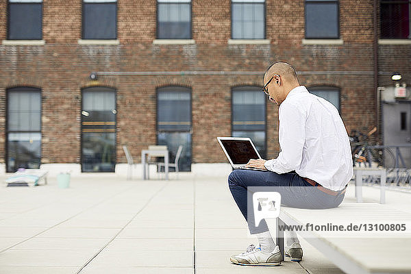 Full length of businessman using laptop computer while sitting on lounge chair at building terrace