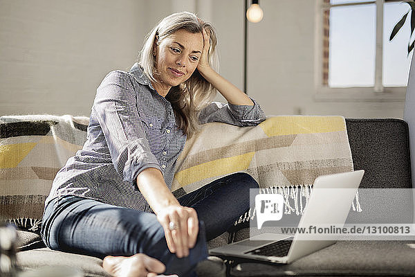 Relaxed woman with laptop sitting on sofa
