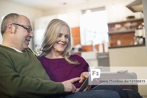 Smiling couple using tablet computer while sitting on sofa at home
