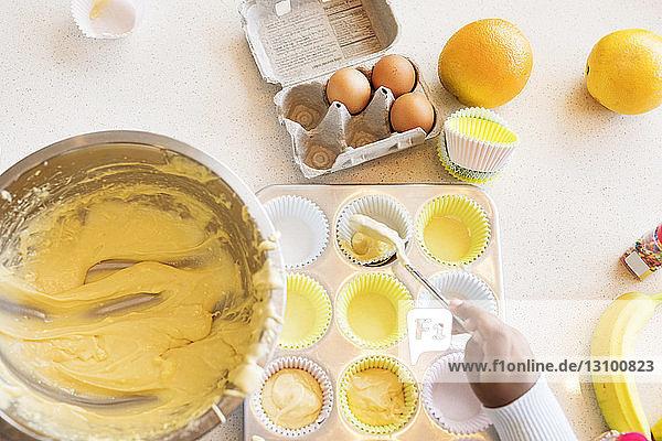 Ausgeschnittenes Bild eines Mädchens  das Teig in einen Cupcake-Halter füllt