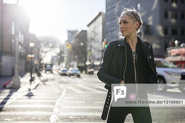 Frau mit Händen in den Taschen  die bei sonnigem Wetter beim Spaziergang auf der Stadtstraße wegschaut