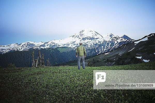 Rear view of man standing on grassy field against mountain