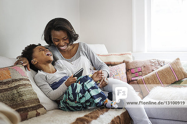 Boy laughing while using tablet computer with mother on sofa at home