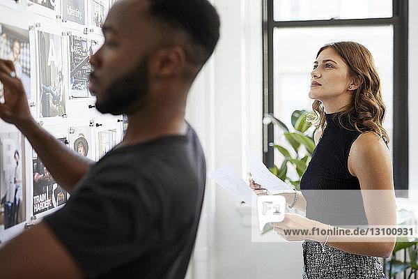 Geschäftsfrau betrachtet Fotoausdrucke am Schwarzen Brett  während ein männlicher Kollege im Vordergrund arbeitet