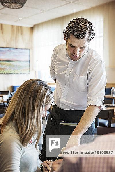 Kellner,  der Frau im Restaurant hilft