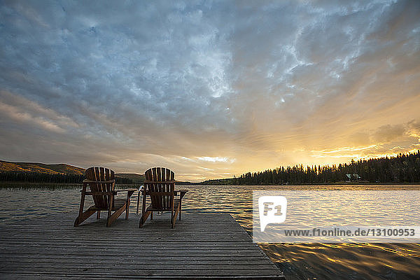 Chairs on pier by Lac Le Jeune lake at Paul Lake Provincial Park against sky during sunset
