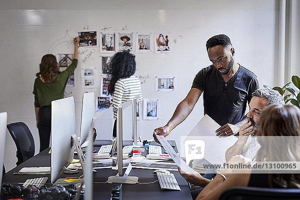 Geschäftsleute sehen sich Dokumente an,  während weibliche Kollegen am Schwarzen Brett im Büro arbeiten