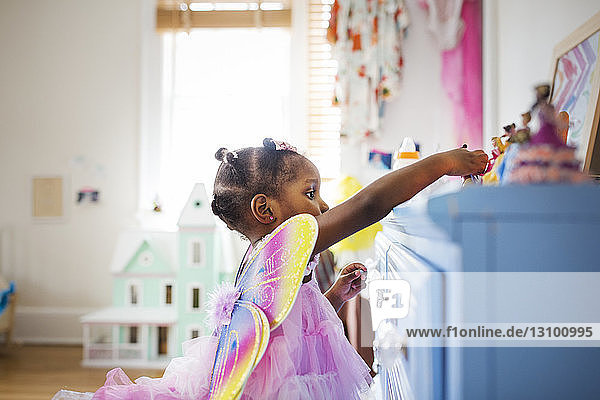 Side view of girl dressed in fairy costume playing with toys at home