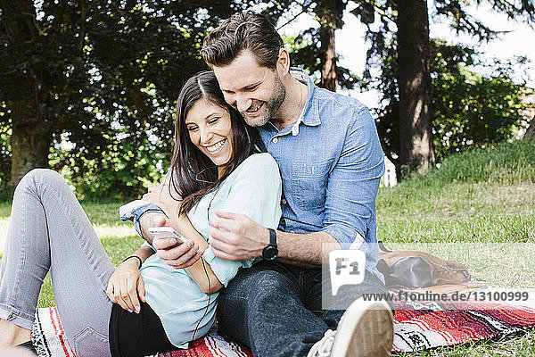 Glückliches Paar telefoniert im Park sitzend per Handy
