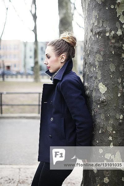 Seitenansicht einer nachdenklichen Frau  die sich an einen Baumstamm lehnt