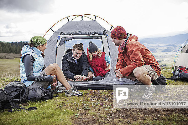 Friends camping on field against sky