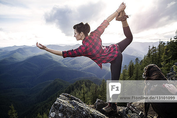 Woman standing on one leg at mountain cliff