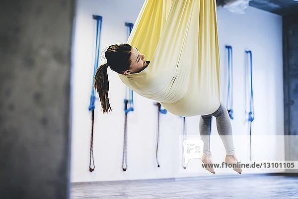Junge Frau hängt in Hängematte  während sie im Fitnessstudio Yoga praktiziert
