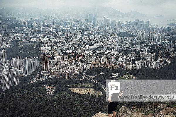 Hochwinkelansicht eines Mannes  der auf einem Felsen stehend das Stadtbild betrachtet