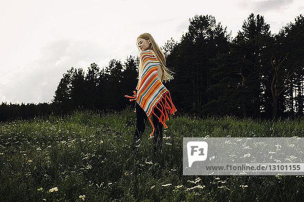Rear view of woman wearing poncho walking on grassy field against sky