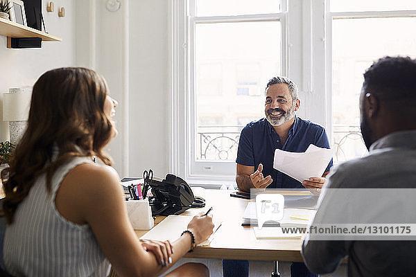 Lächelnder Geschäftsmann erklärt Kollegen im Kreativbüro Dokumente
