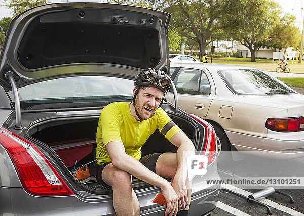 Tired male cyclist sitting in car trunk