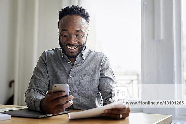 Lächelnder Geschäftsmann benutzt Mobiltelefon  während er im Büro am Schreibtisch sitzt