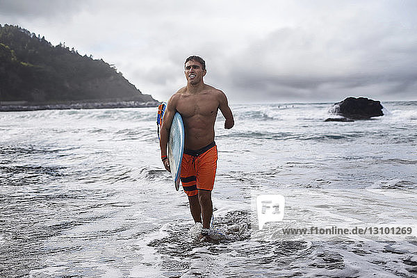 Disabled man carrying surfboard while walking out of sea against sky