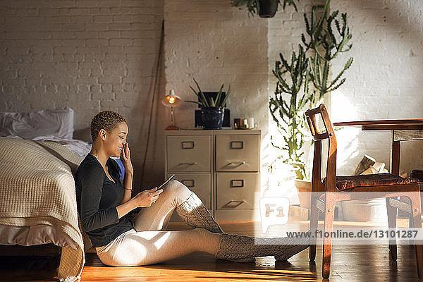 Seitenansicht einer glücklichen Frau  die einen Tablet-Computer benutzt  während sie im Schlafzimmer auf dem Boden sitzt