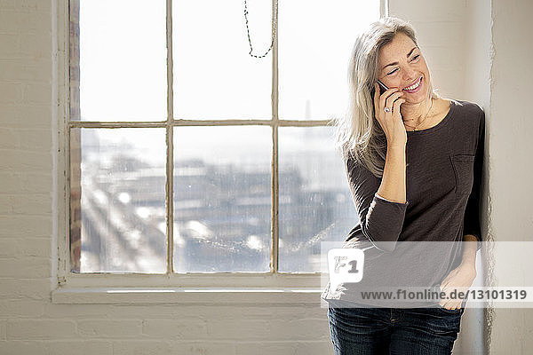 Happy mature woman talking on phone while leaning on wall at home