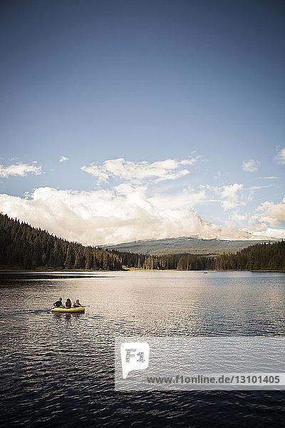 Friends rafting in river against sky