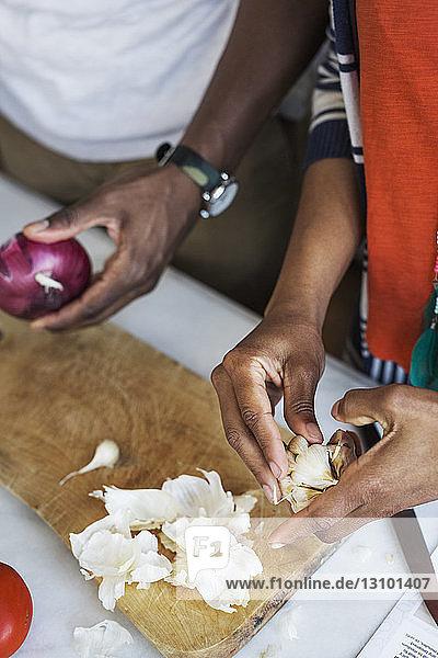 Ausgeschnittenes Bild einer Frau  die mit ihrem Freund in der Küche Knoblauch schält