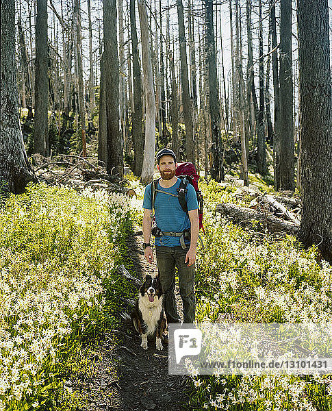 Portrait of man with dog standing on trail amidst plants